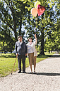 Senior couple with balloons in a park - UUF10647
