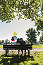 Happy senior couple with balloons kissing on bench in a park - UUF10650