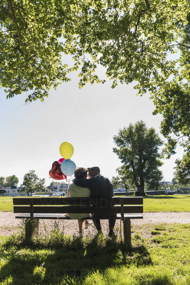 Happy senior couple with balloons kissing on bench in a park - UUF10650 - Uwe Umstätter/Westend61