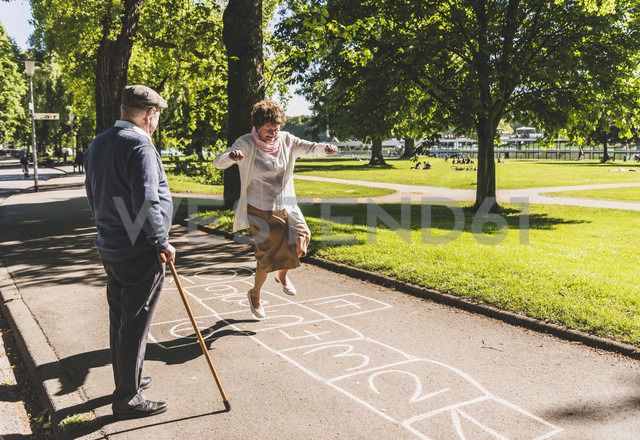 Senior woman playing hopscotch while husband watching her - UUF10653 - Uwe Umstätter/Westend61