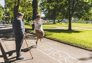 Senior woman playing hopscotch while husband watching her - UUF10653