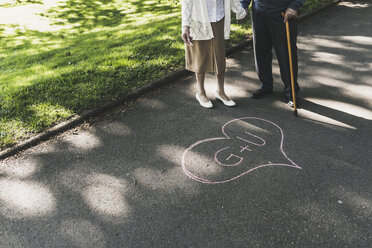 Senior couple drawed love heart with initials on tarmac - UUF10656
