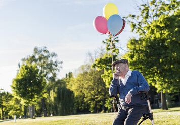 Pensive senior man with balloons sitting on his wheeled walker in nature - UUF10668