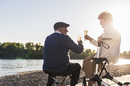 Senior couple toasting with sparkling wine at sunset - UUF10671