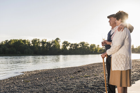 Senior couple on the beach with Champagne glasses at sunset - UUF10674