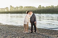 Happy senior couple kissing on the beach - UUF10680