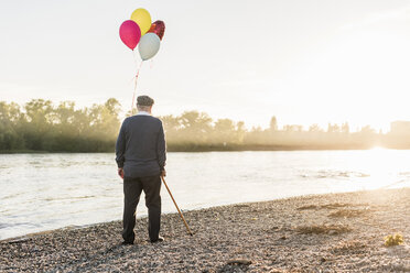 Back view of senior man with balloons standing at riverside in the evening - UUF10683