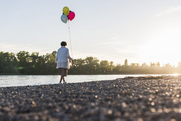 Back view of senior woman with balloons strolling at riverside - UUF10686