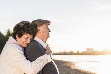 Happy senior couple on the beach at sunset - UUF10689