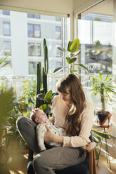 Mother looking at her newborn baby boy at home - MFF03570