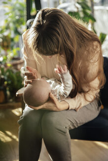 Mother caressing her newborn baby boy at home - MFF03573
