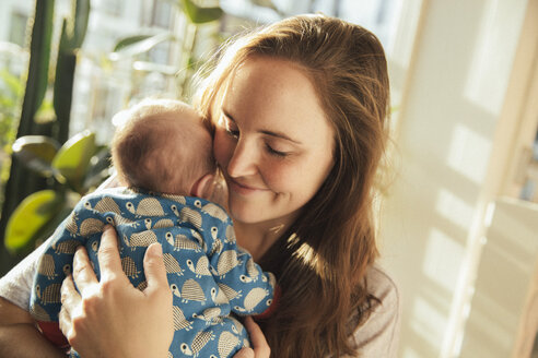 Mother holding her newborn baby boy at home - MFF03579