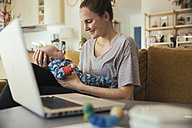 Mother holding her newborn baby at home next to laptop - MFF03582
