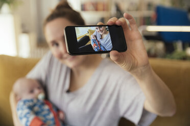 Mother taking a selfie with her newborn baby at home - MFF03585