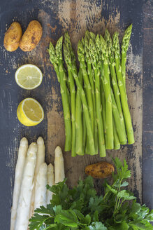 Green and white asparagus, potatoes, sliced lemon and flat leaf parsley on wood - ODF01505