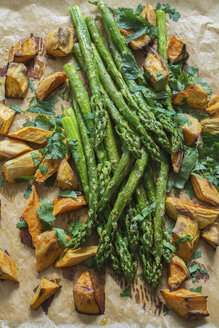 Baked green asparagus, sweet potatoes and flat leaf parsley on baking paper - ODF01508