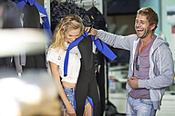 Happy couple shopping for wetsuit in shop - ZEF13843