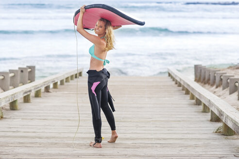 Woman walking to beach with surfboard - ZEF13852