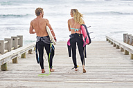 Couple walking to beach with surfboards - ZEF13855