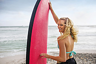 Smiling woman on beach with surfboard - ZEF13858
