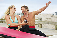 Happy couple with surfboard talking on the beach - ZEF13861