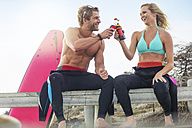 Happy couple with surfboard having a drink on the beach - ZEF13864