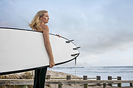 Woman at the ocean with surfboard enjoying the view - ZEF13873