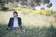 Young man in suit sitting on meadow listening to music - SKCF00308