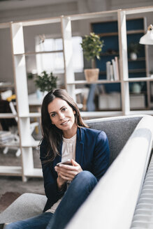 Portrait of confident businesswoman with cell phone on couch - JOSF00964