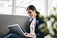 Smiling businesswoman using laptop on couch - JOSF00967