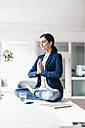 Businesswoman sitting on table meditating - JOSF00970