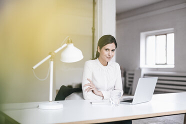 Portrait of businesswoman using laptop at table - JOSF00973