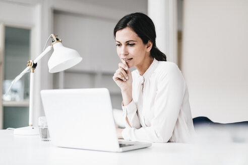 Businesswoman with laptop at table thinking - JOSF00976