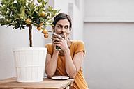 Woman relaxing next to orange tree - JOSF00979