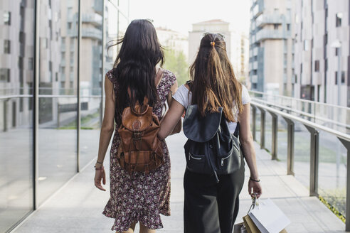 Two young women with backpacks and shopping bags walking in the city - MRAF00185