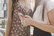 Two young women sharing cell phone in the city - MRAF00188