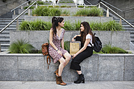 Two young women sitting down and talking in the city - MRAF00194