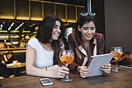 Two happy young women looking at tablet in a bar - MRAF00206