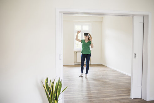 Woman in empty apartment wearing VR glasses - UUF10695