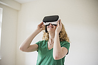Woman wearing VR glasses looking up - UUF10698