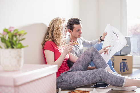 Young couple in new home sitting on floor discussing ground plan - UUF10701