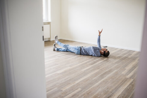 Man lying on the floor in empty apartment wearing VR glasses - UUF10704