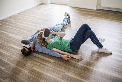 Young couple lying on floor in empty apartment wearing VR glasses - UUF10710