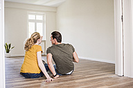 Young couple in new home sitting on floor discussing - UUF10713