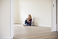 Young woman in new home sitting on floor using tablet - UUF10716