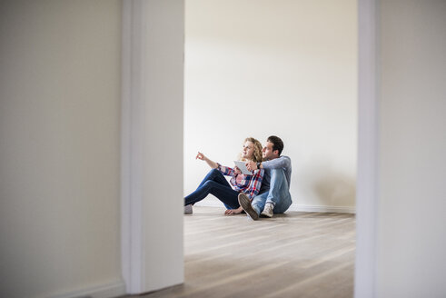 Young couple in new home sitting on floor with tablet - UUF10722