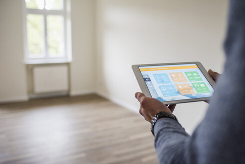 Man in new home using tablet with smart home apps - UUF10725