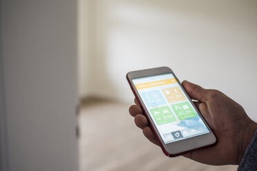 Man at home holding smartphone with smart home apps - UUF10728