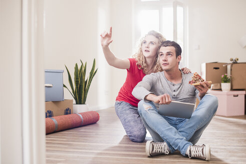 Young couple in new home sitting on floor with tablet - UUF10734