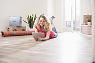 Young woman in new home lying on floor with tablet - UUF10737